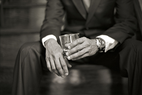 man in suit holding a whiskey glass